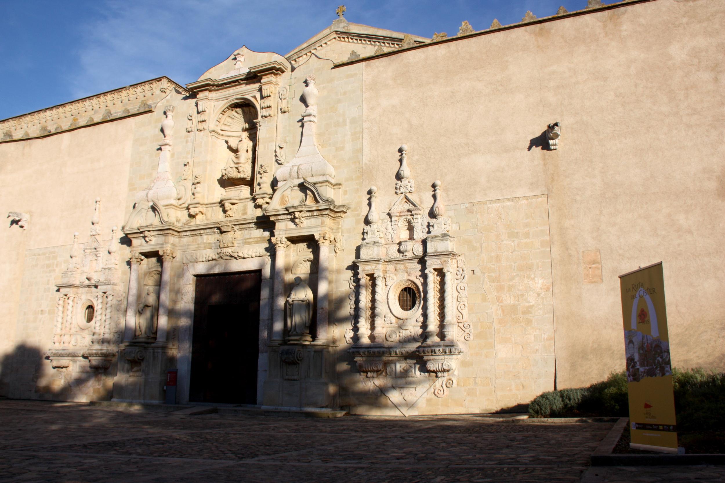 Exterior de l'església del Monestir de Poblet, amb un cartell de La Ruta del Cister a la dreta   ACN