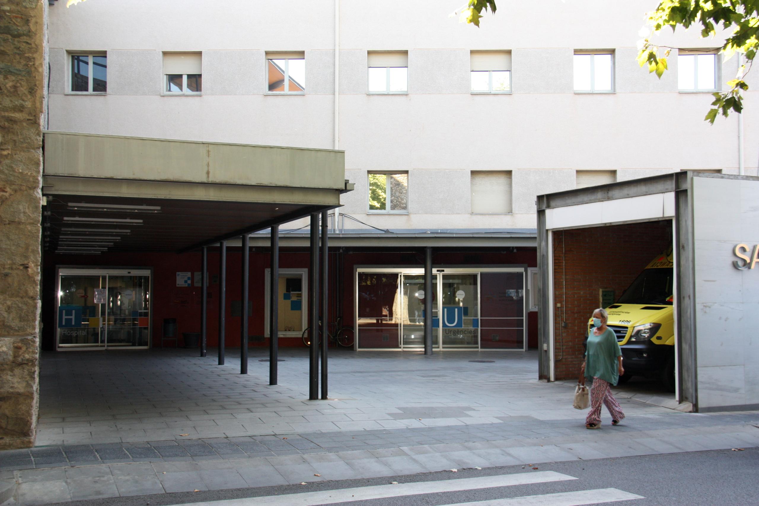 Una de les entrades del Sant Hospital de la Seu d'Urgell i una persona passant pel davant amb mascareta / ACN