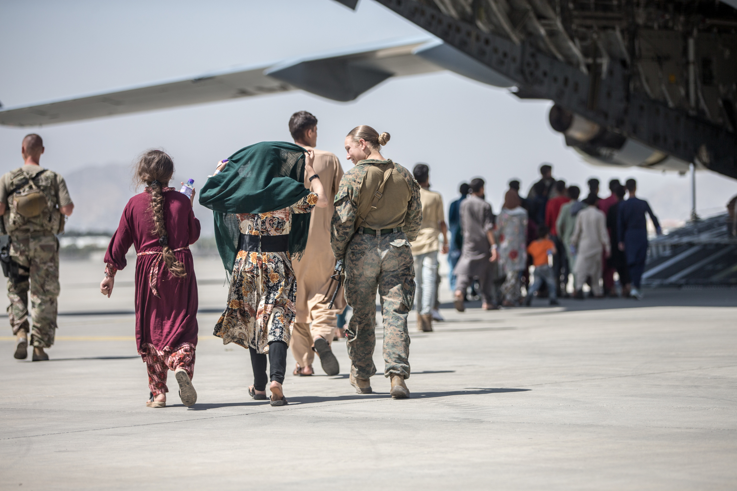 Un marí dels Estats Units escorta nens afganesos durant una evacuació a l'aeroport de Kabul / Europa Press