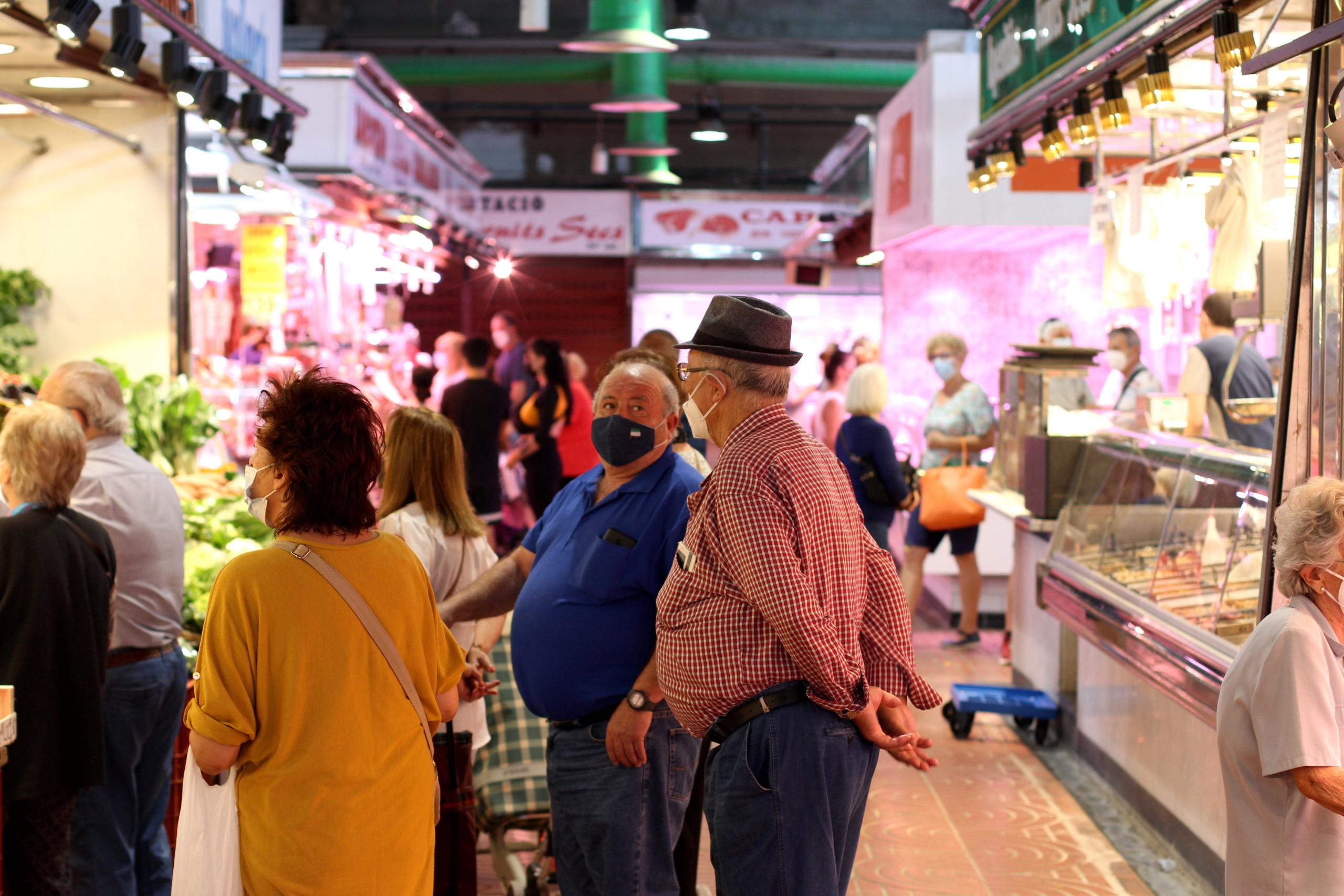 Clients del mercat de Sant Ildefons, de Cornellà  de Llobregat, fent cua en una parada / Marc Solanes