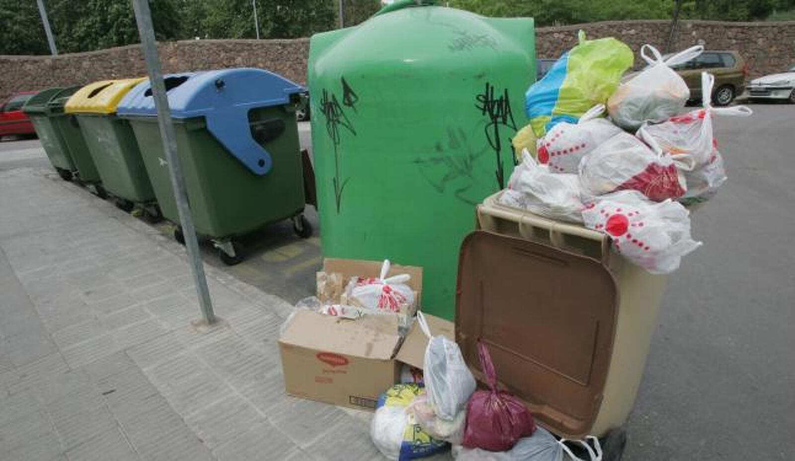 Piles de bosses de brossa en un dels contenidors de Terrassa