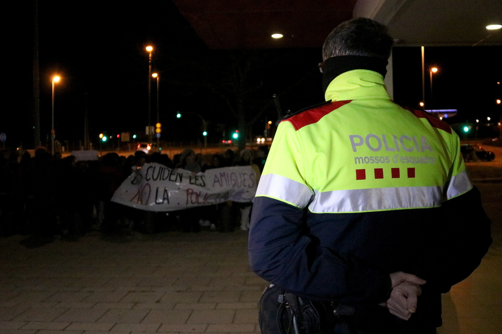 Un agent dels mossos amb la manifestació contra la violència contra les dones al davant