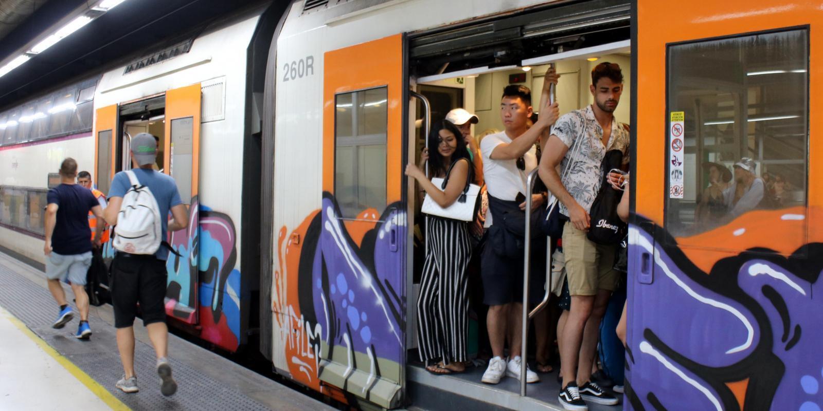 Viatgers a la porta d'un tren de Rodalies a l'estació de Sants