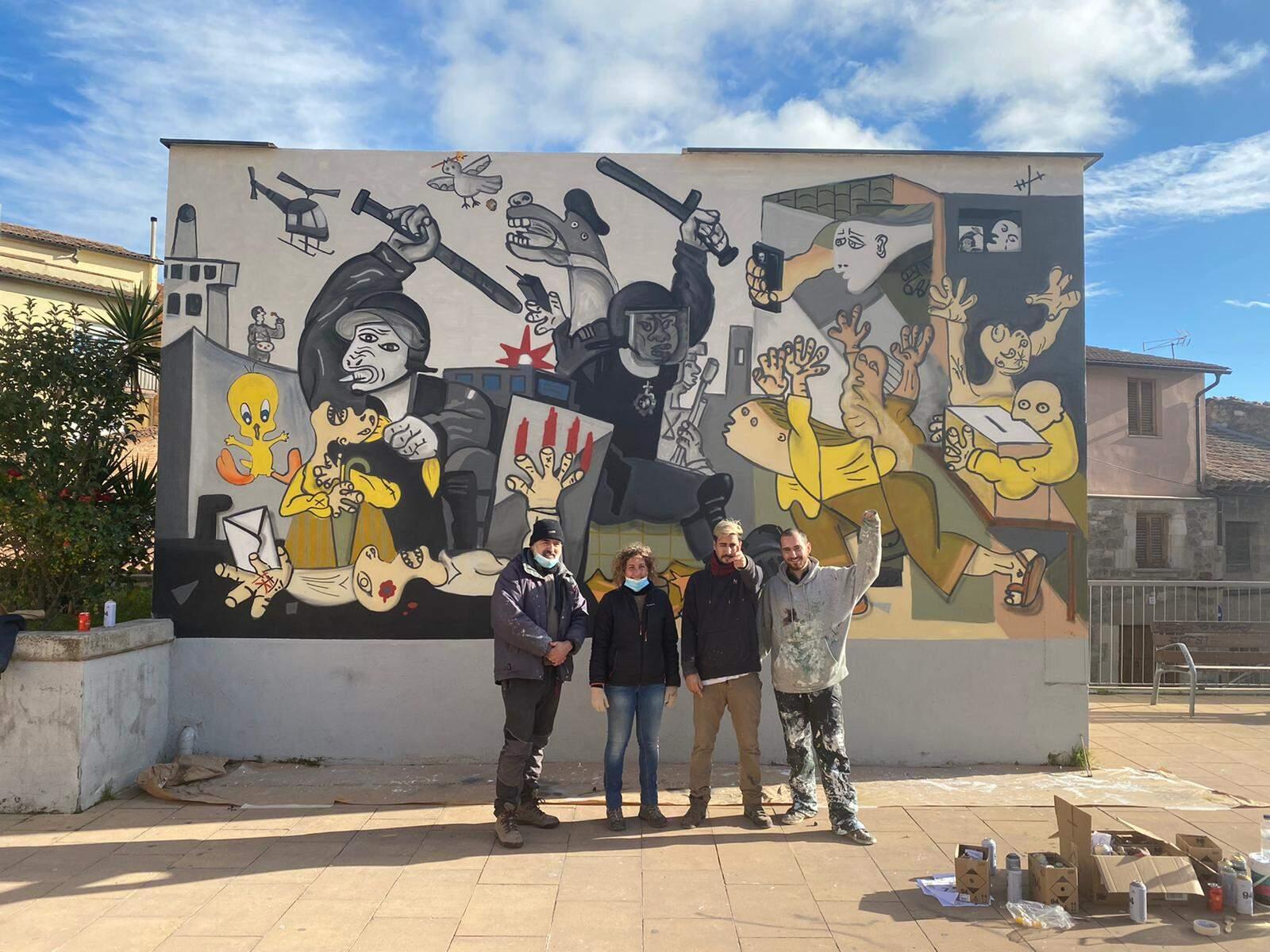 Els artistes davant del mural recuperat