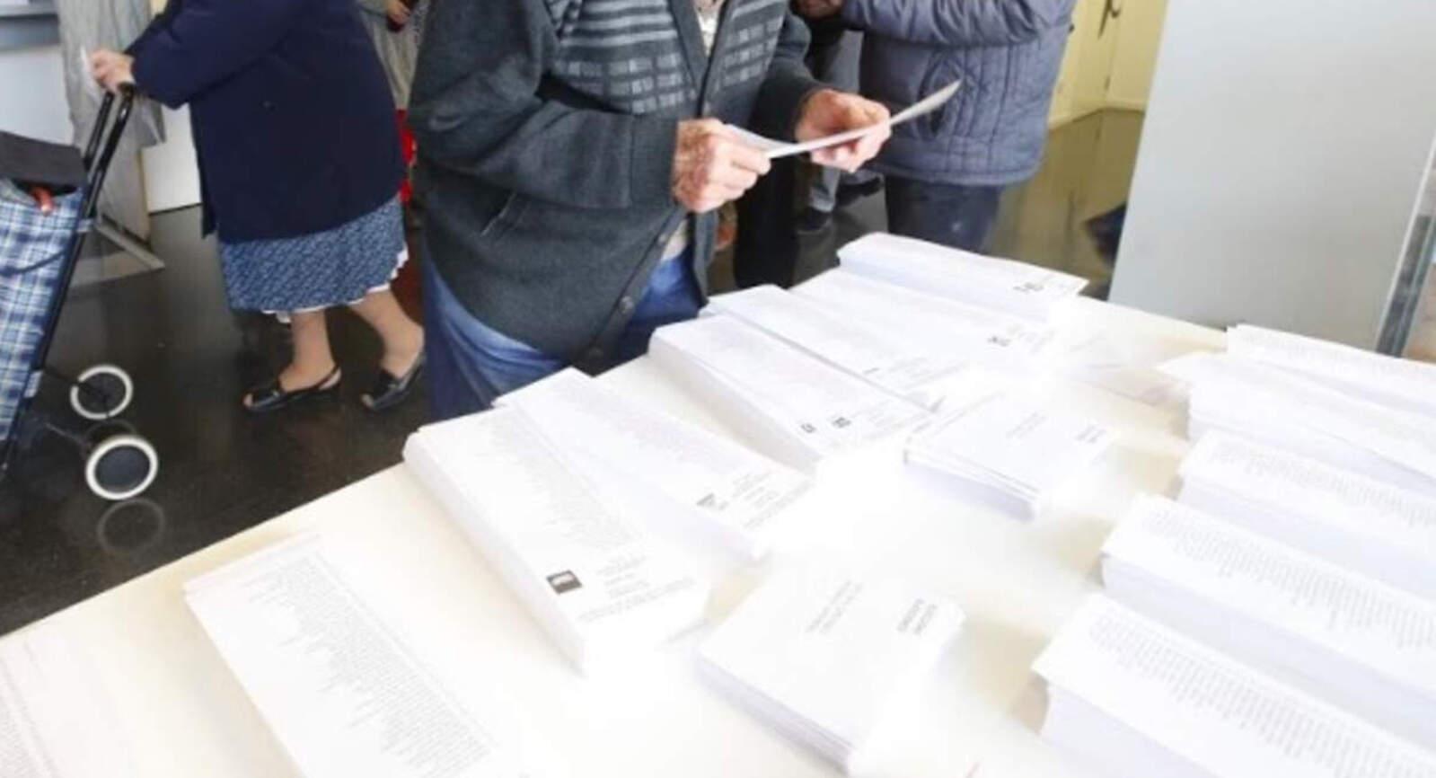 Un egarenc mirant les paperetes de votació el 2017
