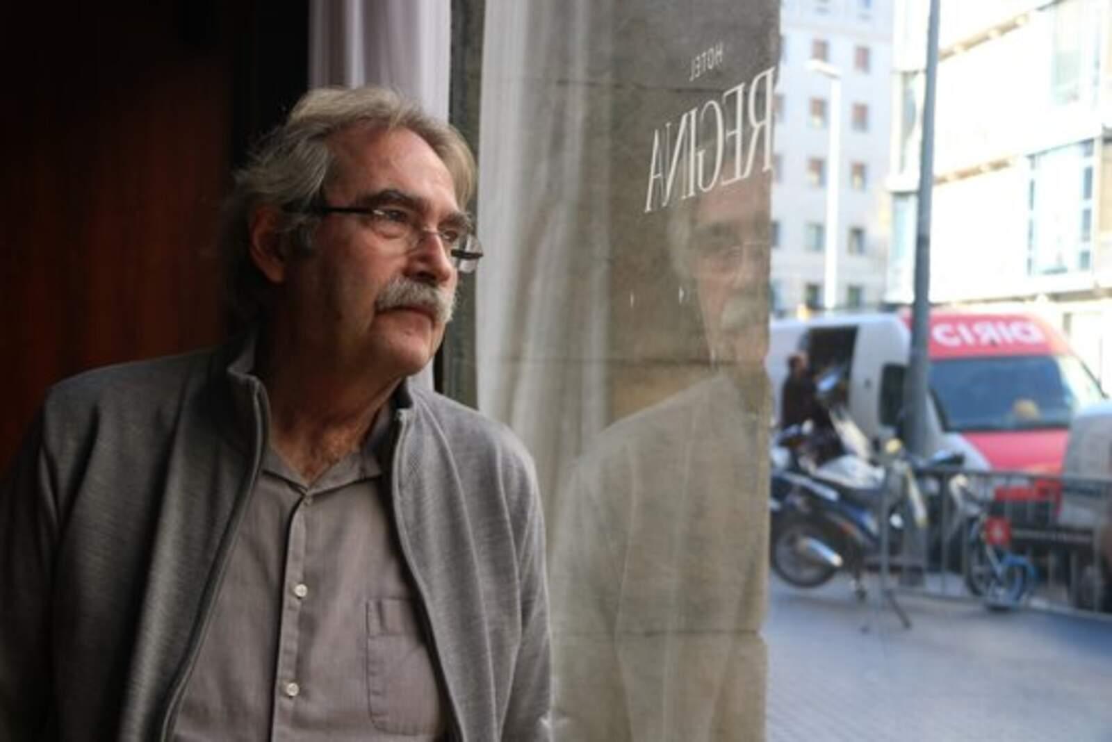 L'escriptor Jaume Cabré mirant a través d'un vidre el carrer, amb el seu reflex, durant una entrevista amb l'ACN