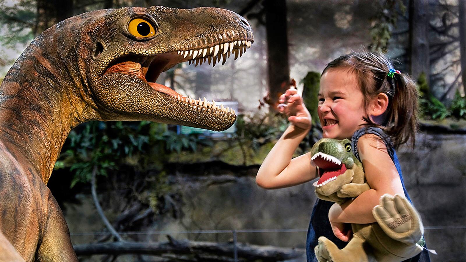 Una nena gaudint amb la reproducció d'un dinosaure   Dinosaurs Tour