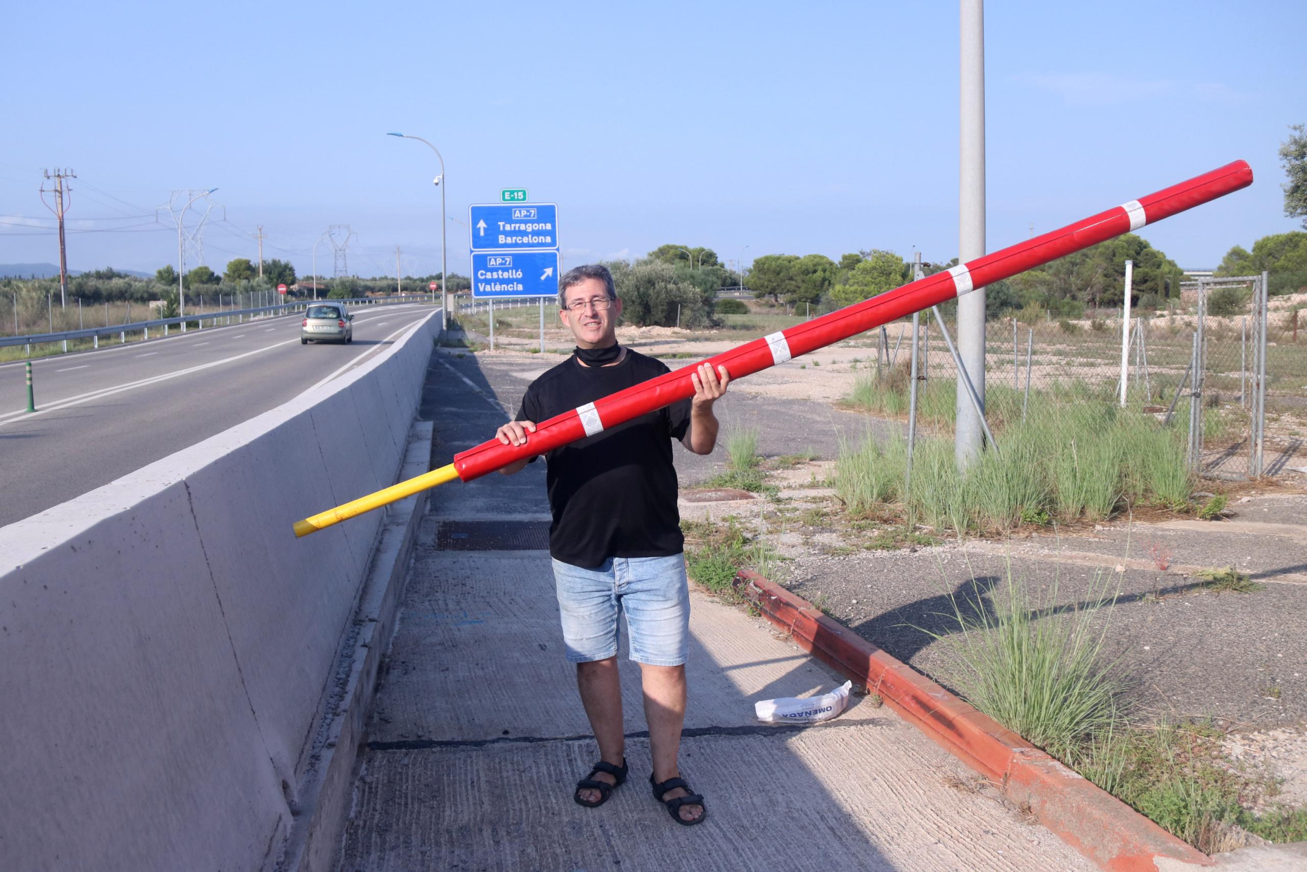 Pla obert de l'activista per l'alliberament de l'AP-7, Llorenç Navarro, amb una de les barreres a l'antic peatge de l'Aldea. Imatge del 26 d'agost de 2021. (Horitzontal)
