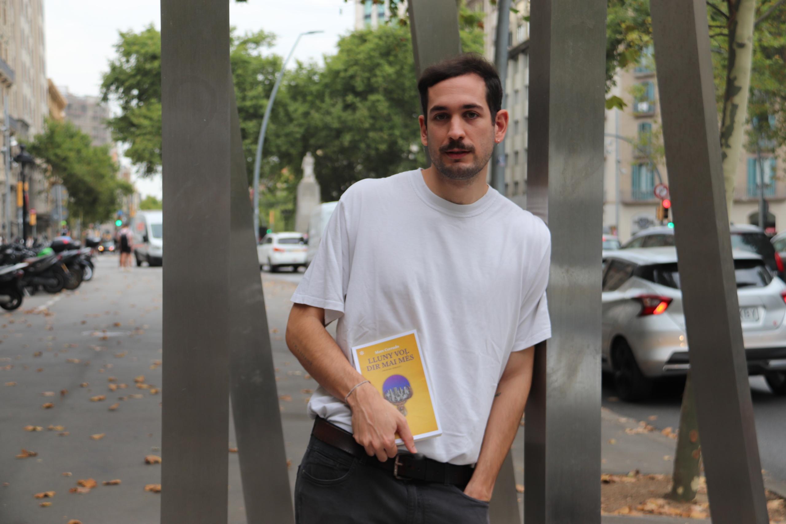 L'escriptor Marc Cerrudo amb la seva primera novel·la, 'Lluny vol dir mai més', a la Gran Via de Barcelona | ACN