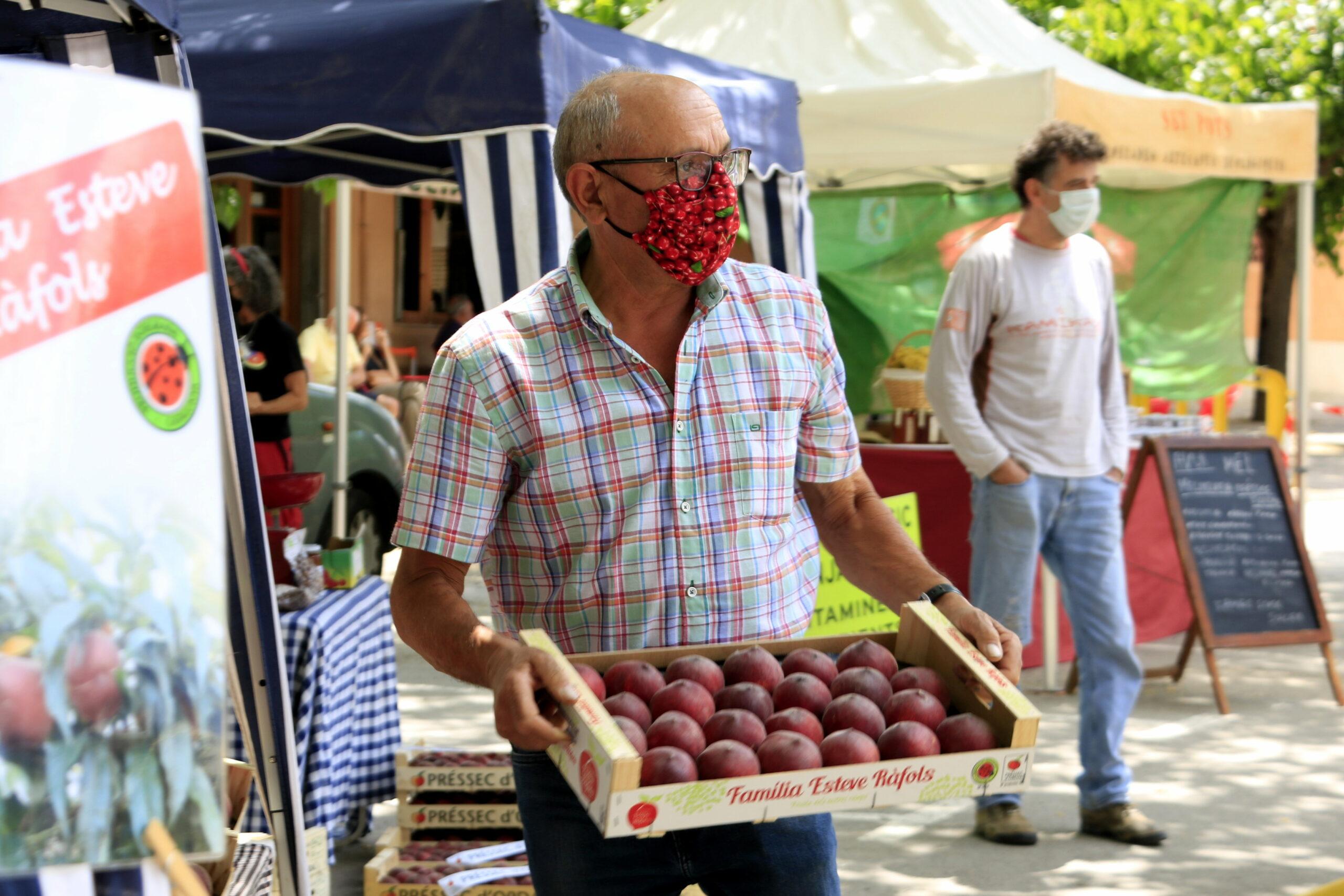 El productor Josep Esteve, de la Família Esteve Ràfols, al Mercat del Préssec d'Ordal; porta una mascareta estampada amb cireres i subjecta una caixa de préssecs | ACN