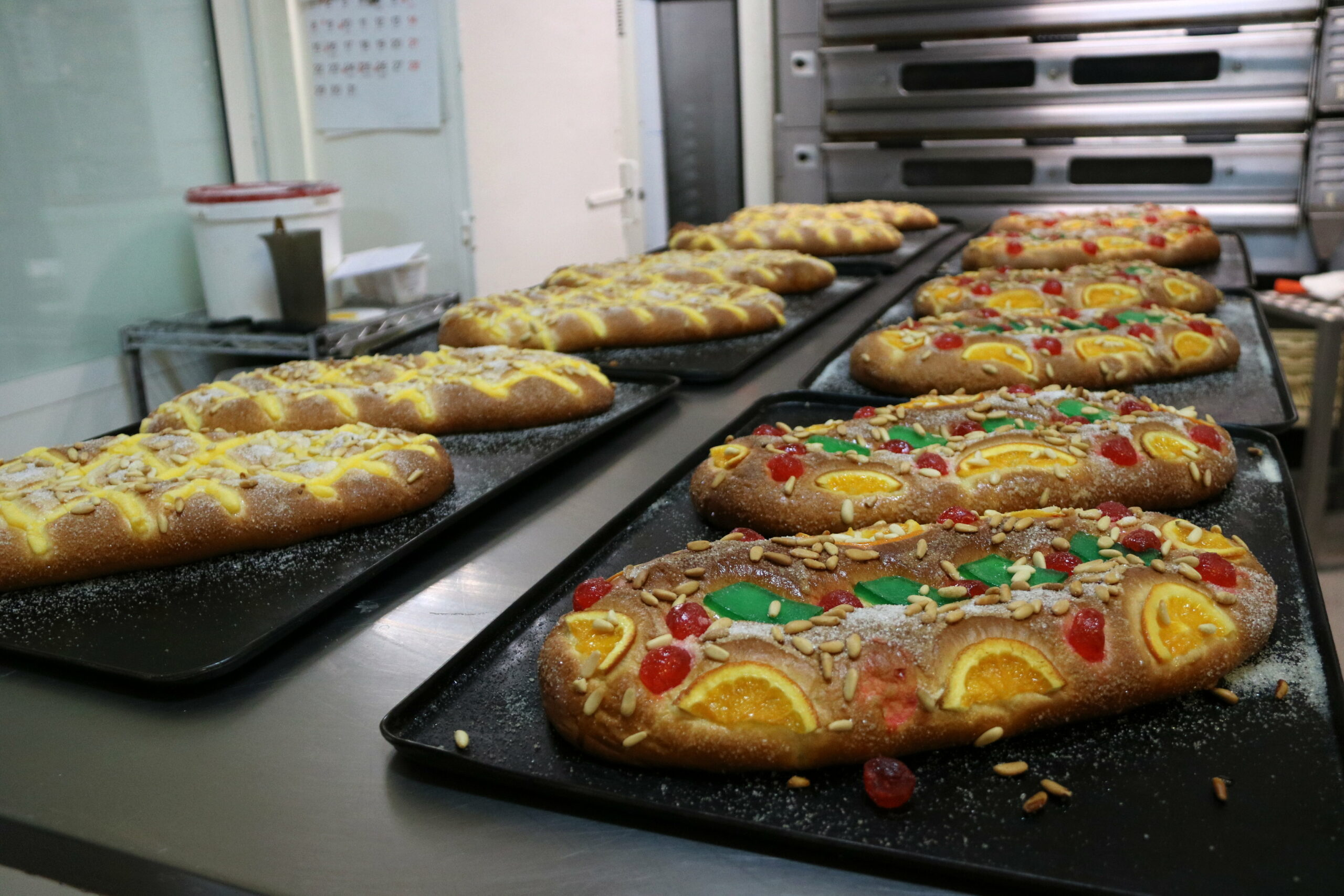 Una filera de coques de Sant Joan acabades de sortir del forn a la pastisseria Lis de Barcelona | ACN