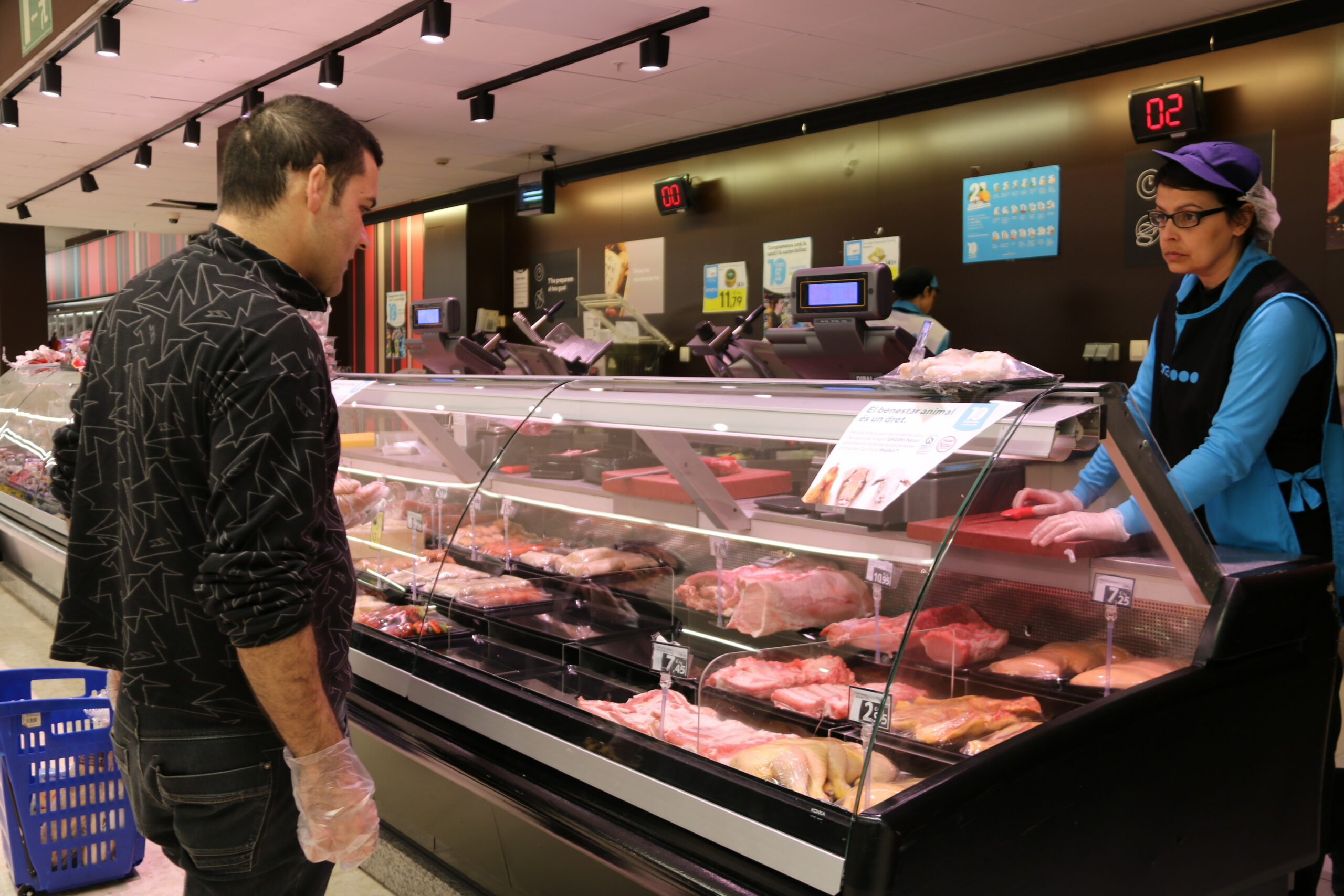 Un client amb guants comprant carn en un supermercat de l'Espai Gironès | ACN