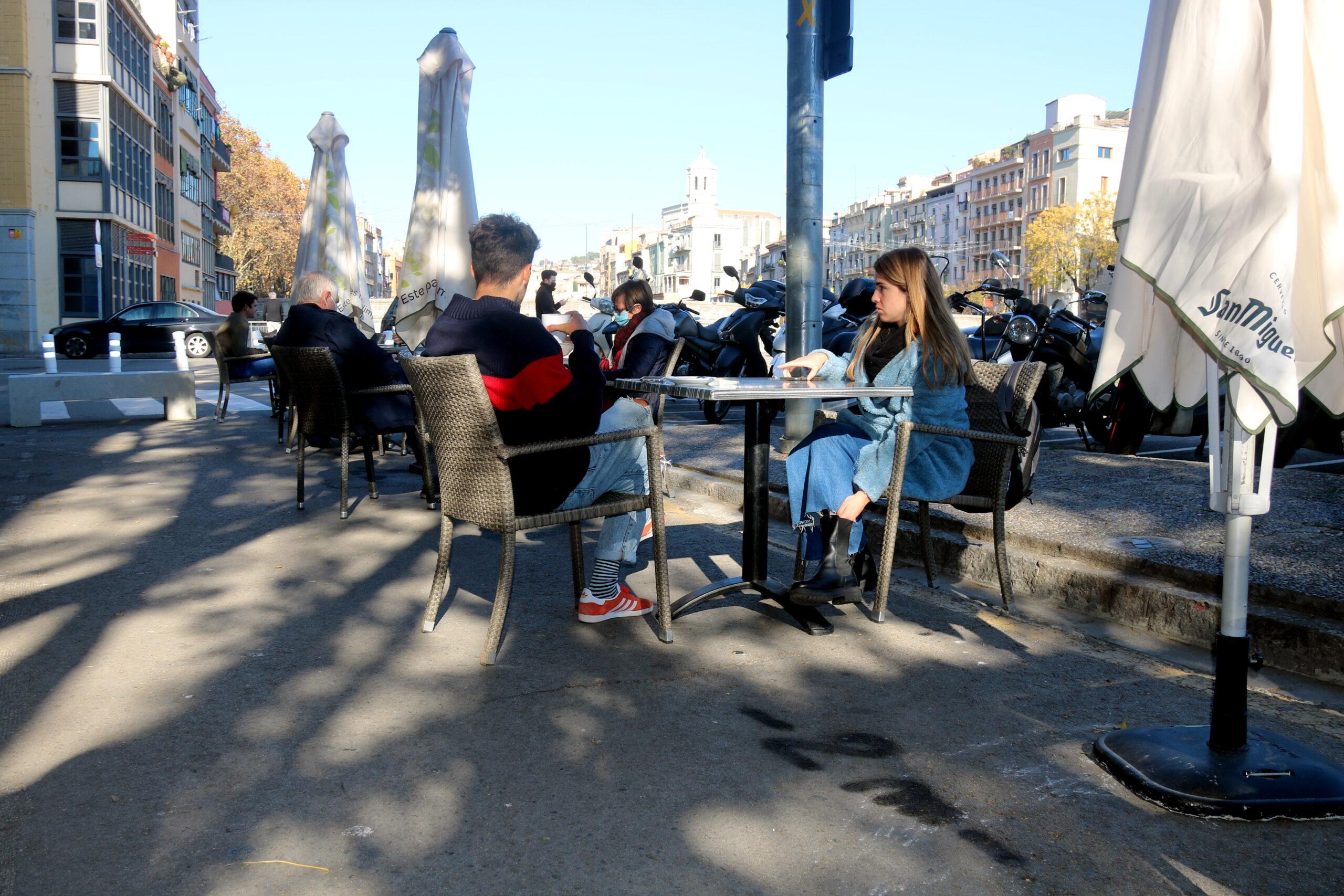 En primer terme, una pintada a l'asfalt que marca la separació de 2 metres; al fons, taules d'un bar a la plaça Catalunya de Girona | ACN