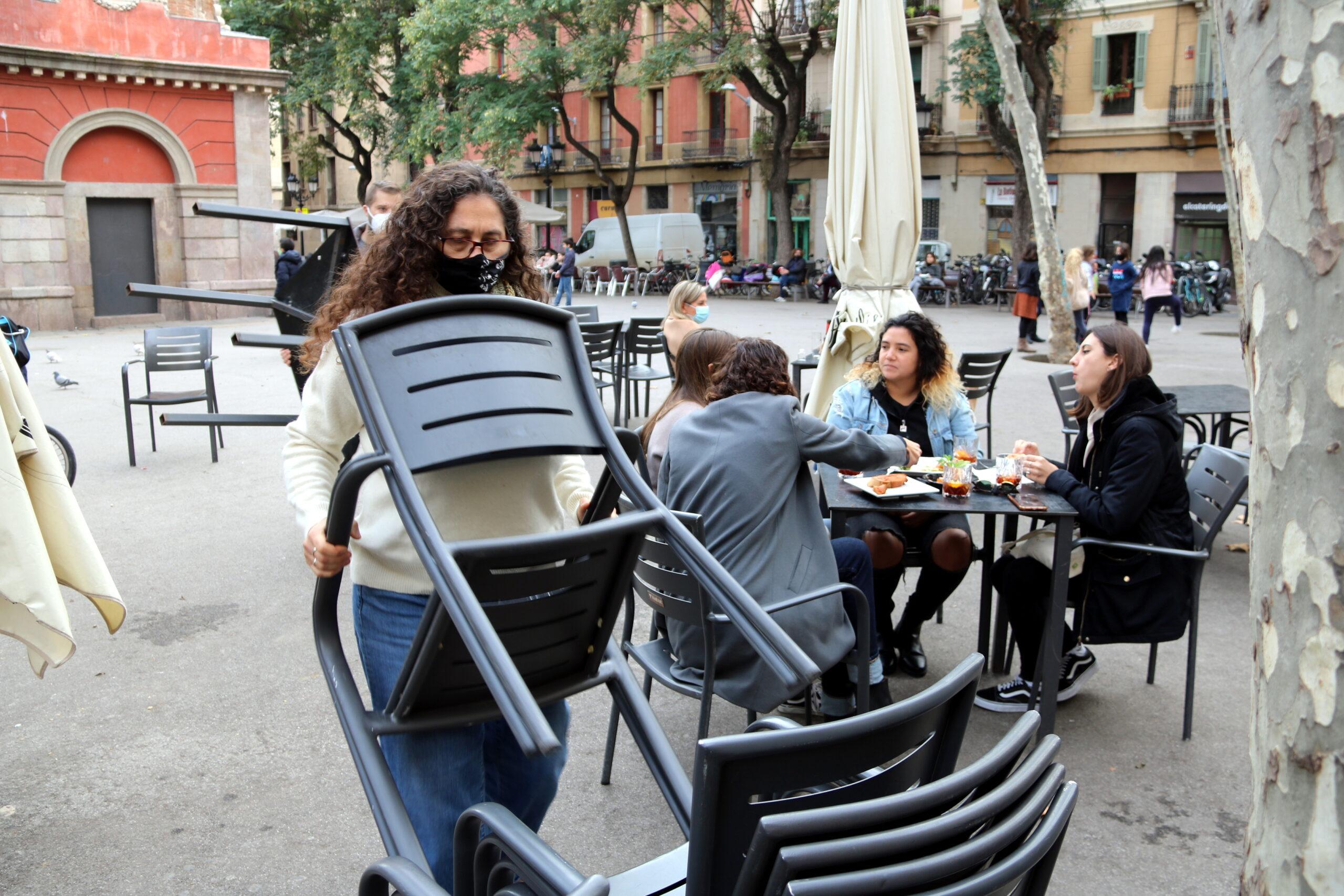 Treballadors del restaurant Amélie de la plaça de la Vila recollint taules i cadires amb gent encara menjant   ACN