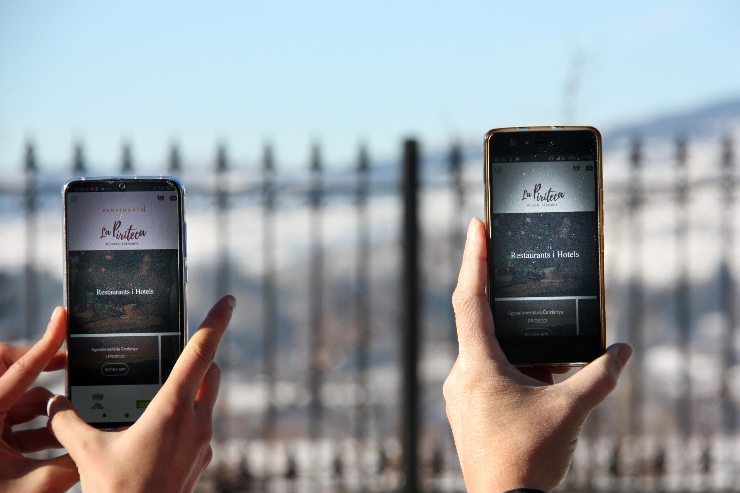 Dos telèfons mòbils amb l'aplicació 'La Piriteca' oberta i un paisatge de la Cerdanya nevada al fons | ACN