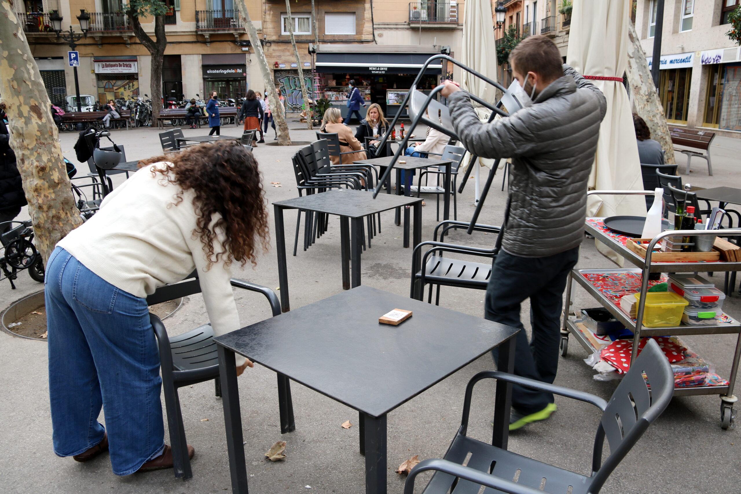 Treballadors del restaurant Amélie de la plaça de la Vila recollint taules i cadires amb gent encara menjant | ACN