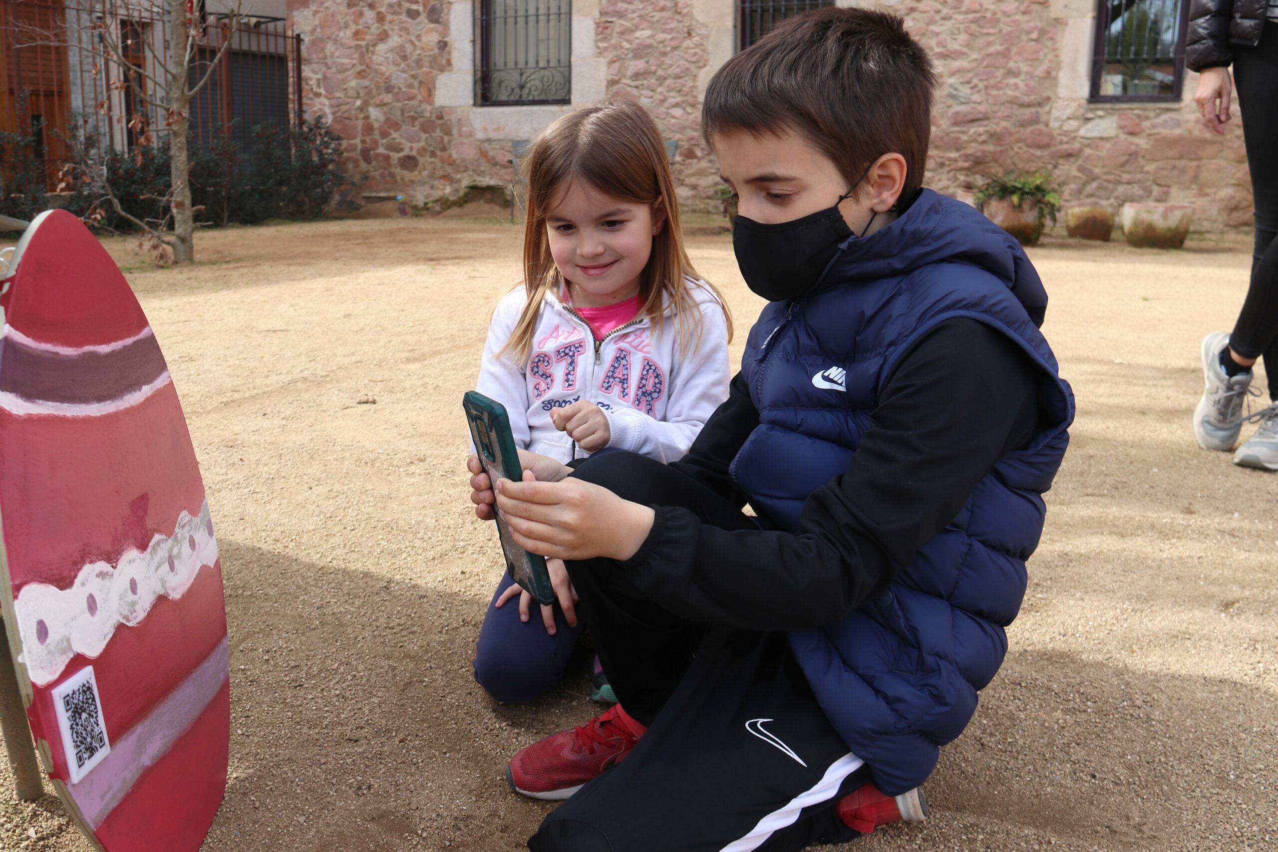 Dos nens fotografiant el codi QR d'un ou de Pasqua en una activitat organitzada per l'Ajuntament de Sant Hilari Sacalm | ACN