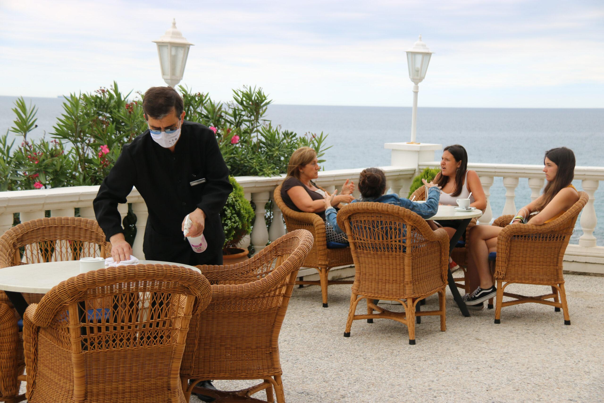Un cambrer desinfectant les cadires de la terrassa de l'Hotel Costa Brava amb unes dones prenent un cafè al darrera | ACN