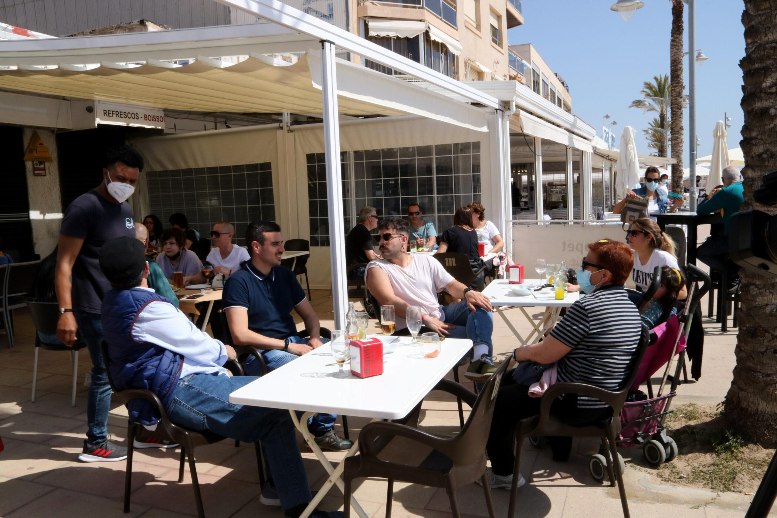 Un grup de persones assegudes en una terrassa d'un bar del passeig marítim de Coma-ruga, al Vendrell | ACN
