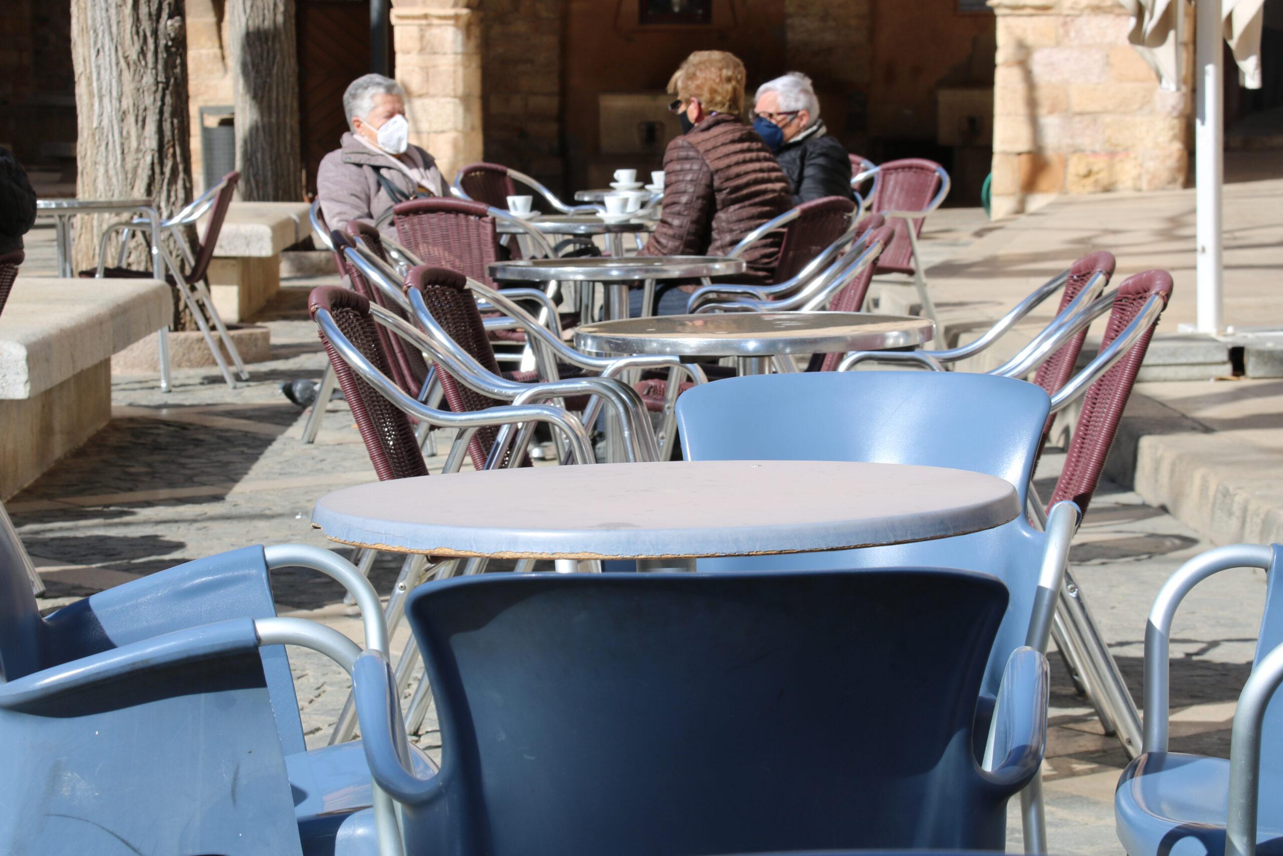 Unes dones consumint a les terrasses de la plaça Major de Montblanc, i taules buides en primer terme | ACN