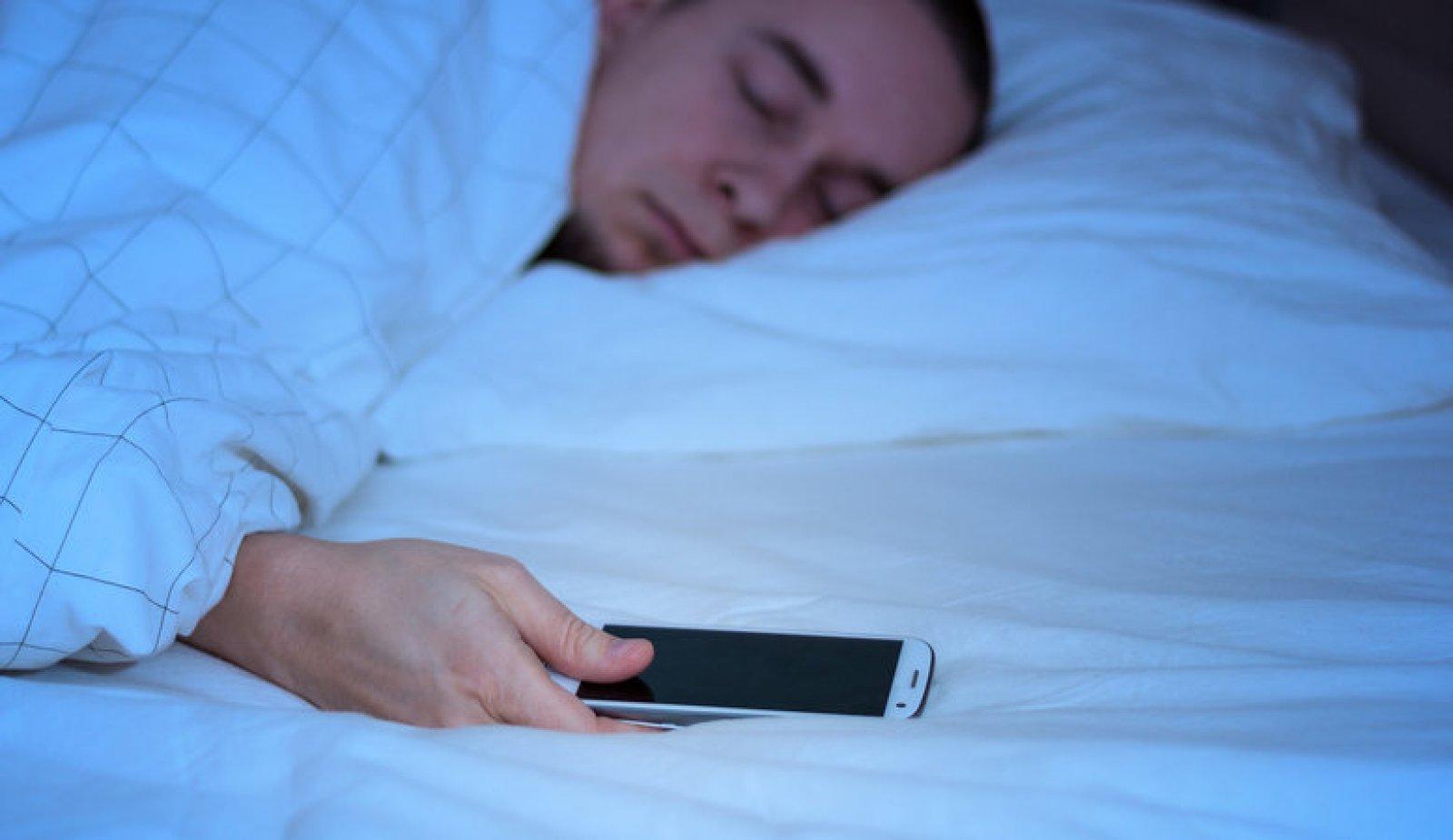 Una persona dorm amb el mòbil a prop