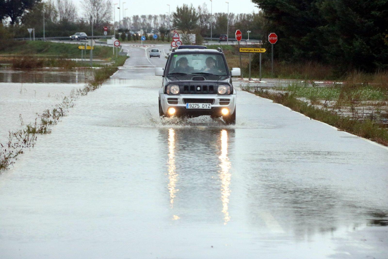 Un cotxe passant per una carretera inundada pel riu Daró aquest diumenge, a Serra de Daró.