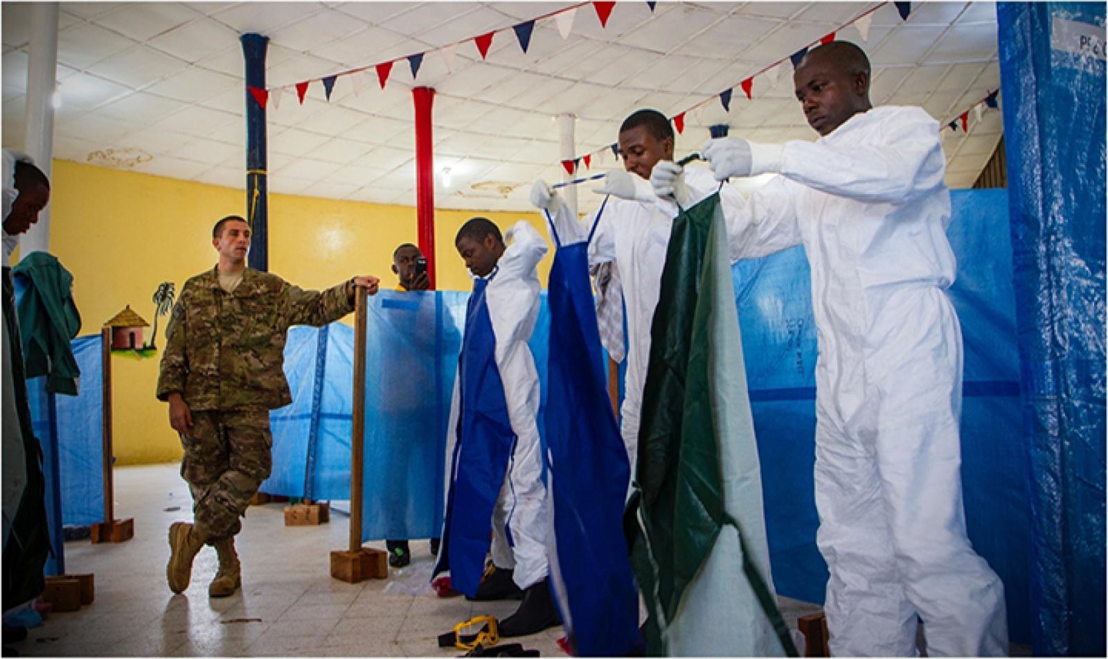 Un oficial mèdic de les forces aèries nord-americanes supervisa la col·locació dels vestits protectors d'un grup de treballadors sanitaris