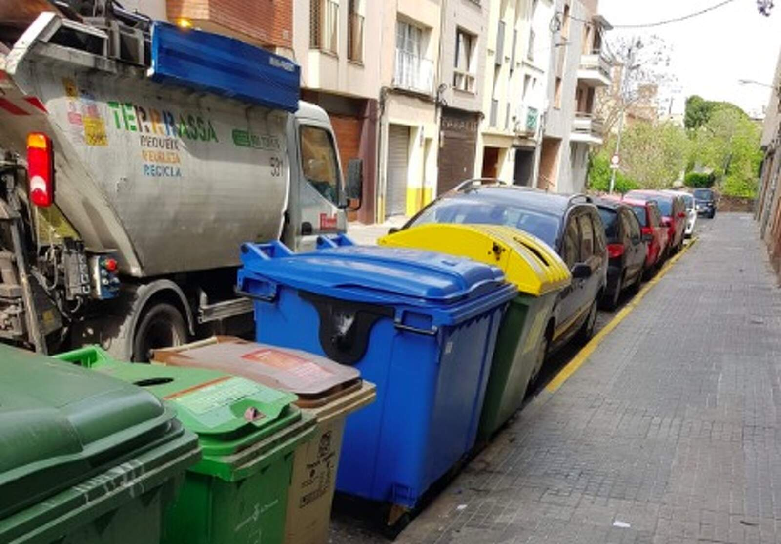 El camió d'Eco-Equip recollint la brossa acumulada al voltant dels contenidors