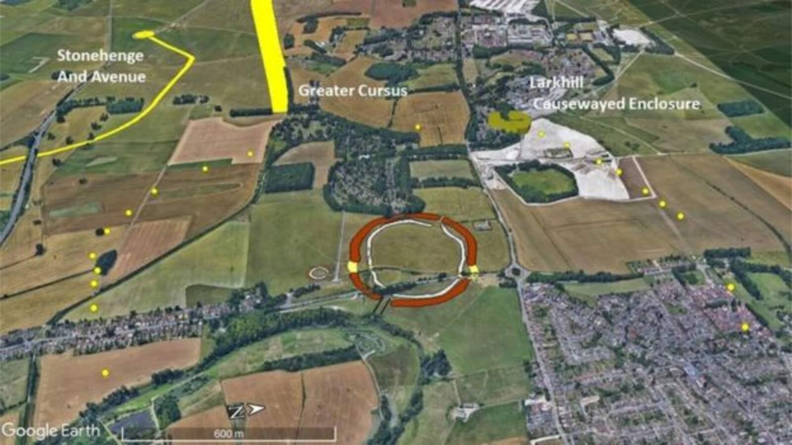 Durrington Walls (vermell) amb el cercle de pous trobat al seu voltant (groc) i Stonehenge a dalt a l'esquerra