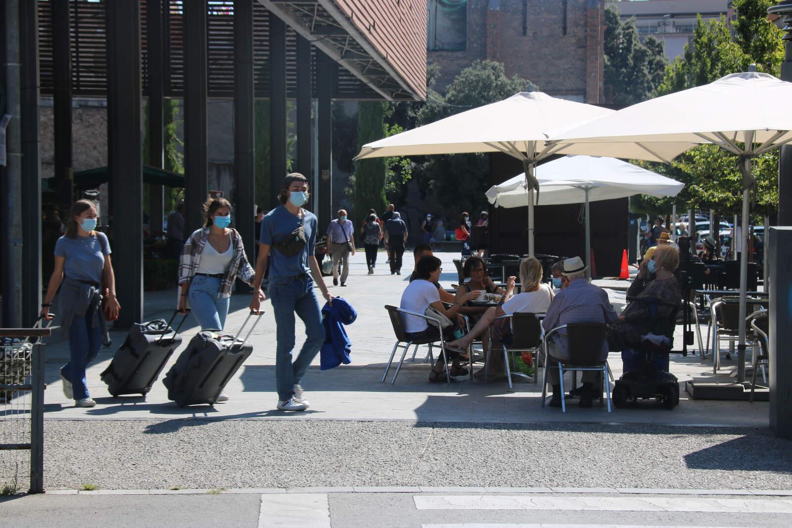 Turistes amb mascareta passant davant d'una terrassa