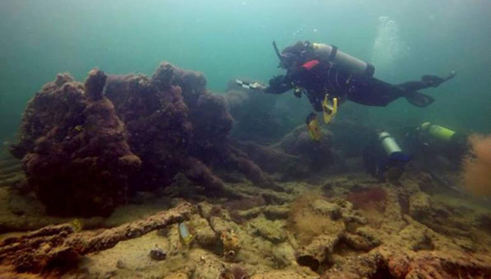Un arqueòleg inspecciona les restes del vaixell