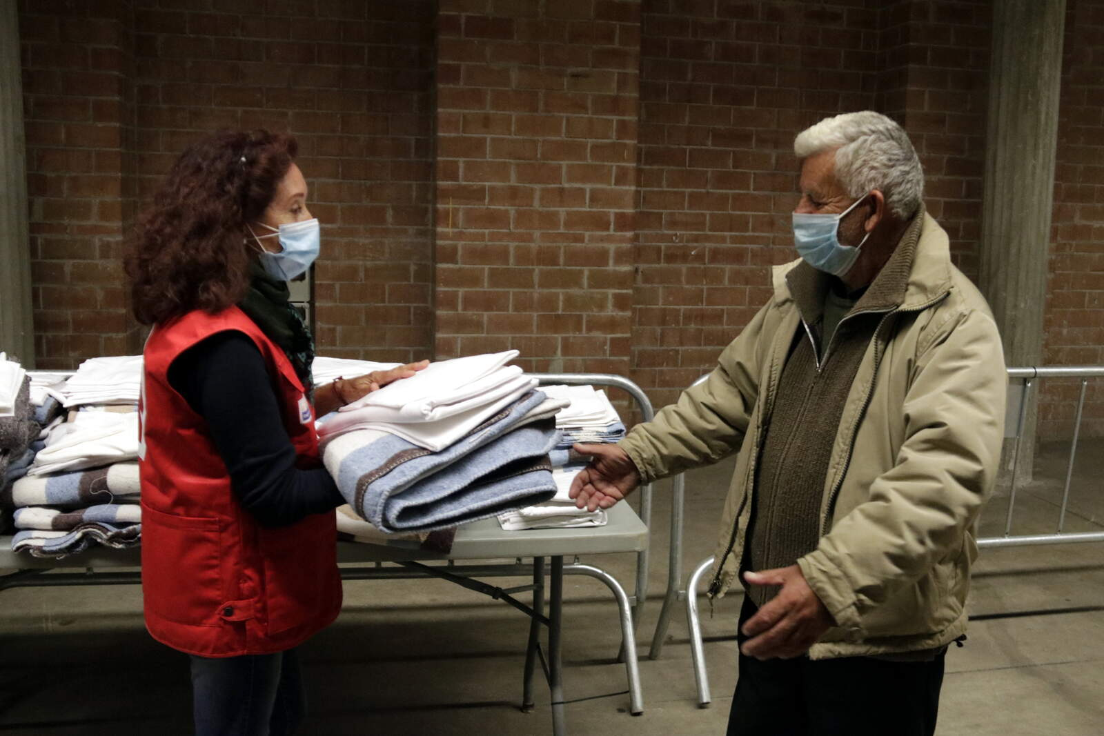 Voluntàries de la Creu Roja donant llençols i mantes a un dels usuaris del Palau de Fires de Girona, l'espai habilitat per l'Ajuntament per als sensesostre