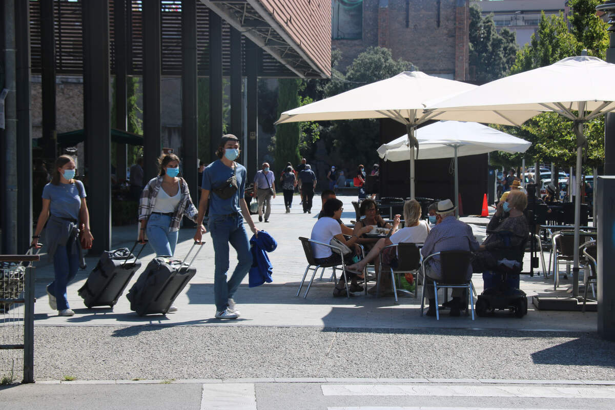 Turistes amb mascareta passant davant d'una terrassa    ACN