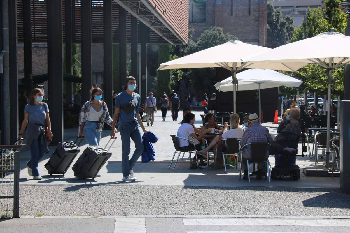 Turistes amb mascareta passant davant d'una terrassa  | ACN