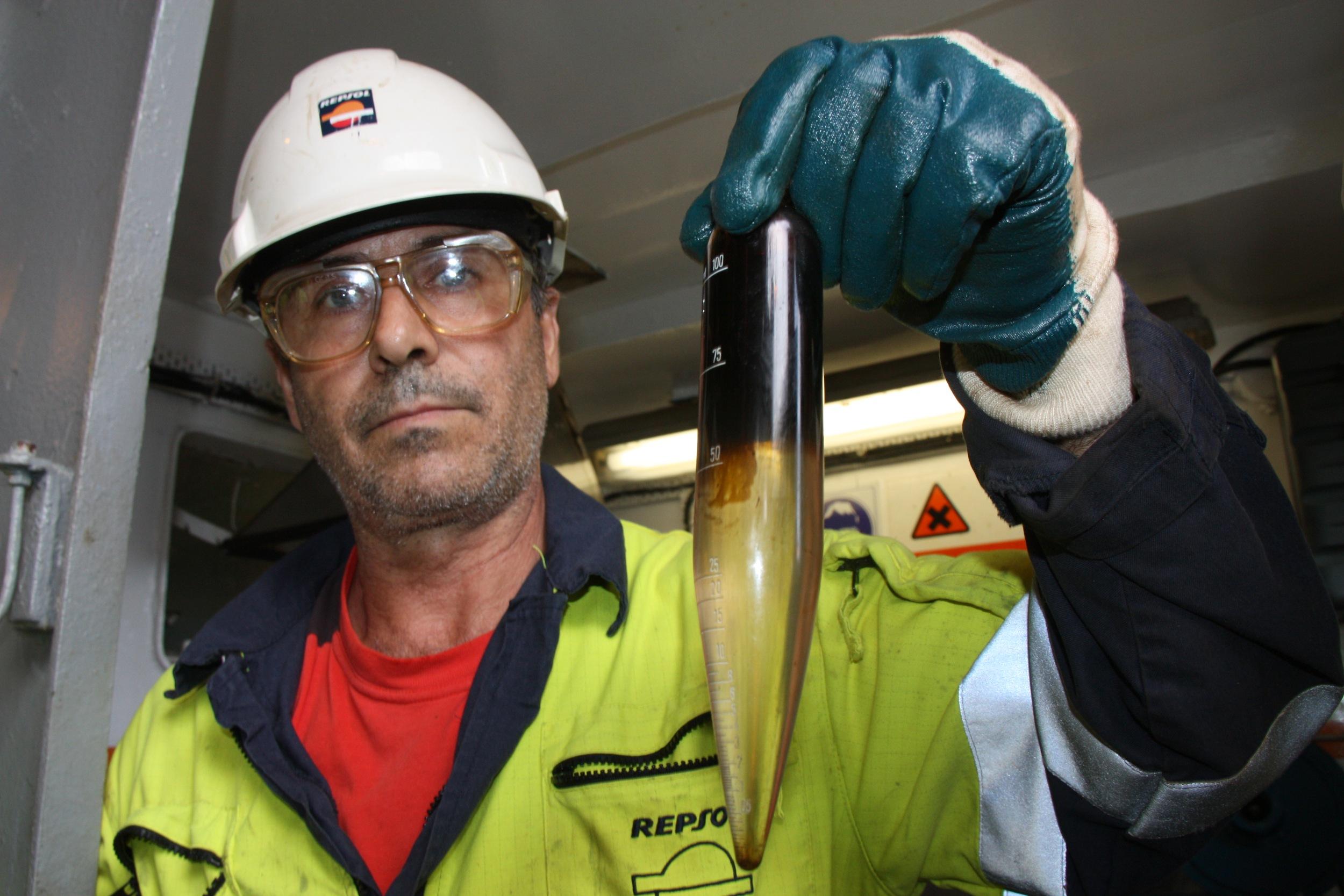 Un treballador de Repsol amb una mostra del petroli produït a la plataforma Casablanca   ACN