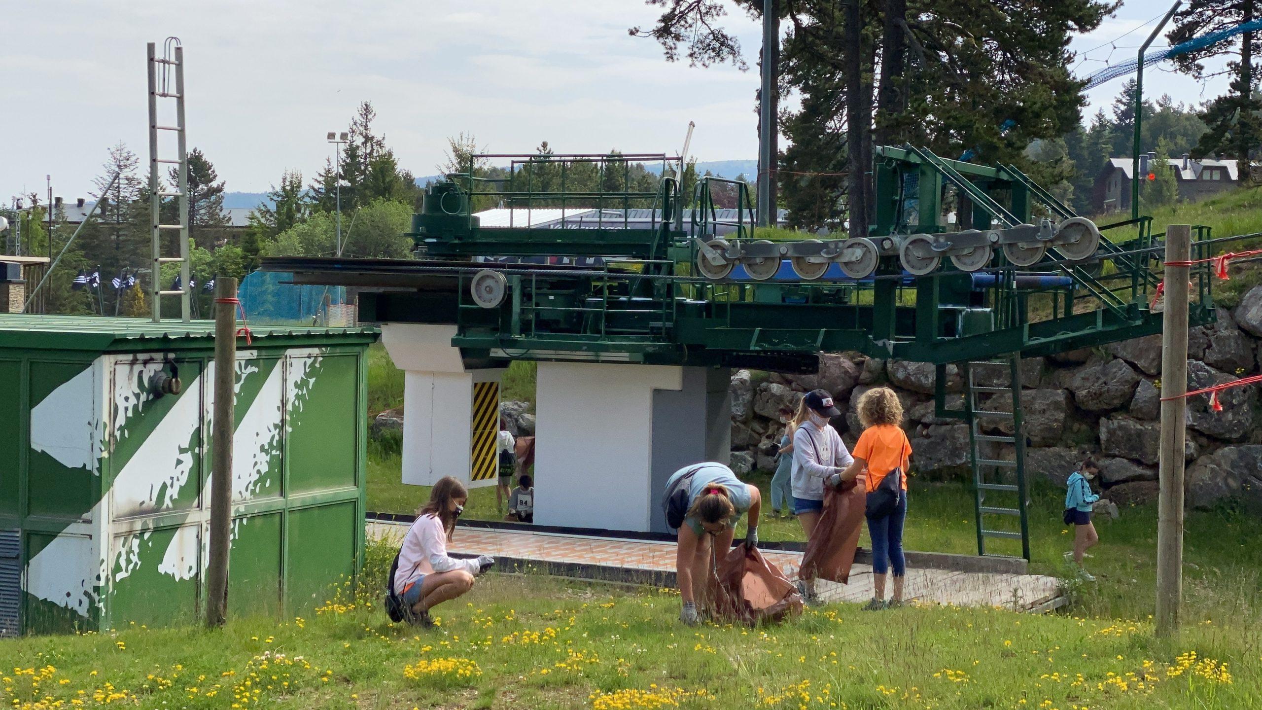 Alumnes de l'Escola Bac de Cerdanya d'Alp recollint residus a l'entorn d'un remuntador de l'estació de La Molina | ACN