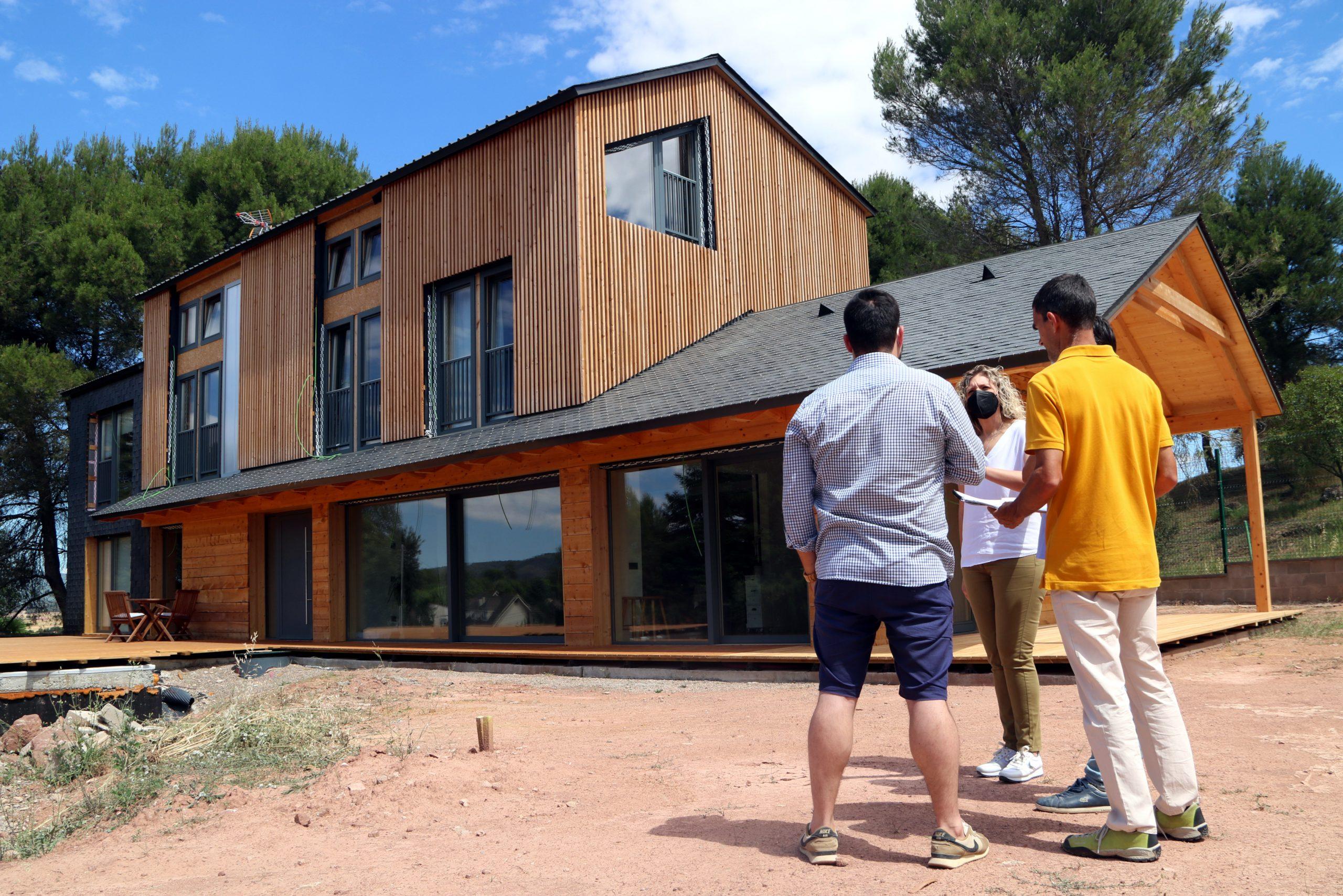 Una casa de fusta, al Bages, amb la seva propietària i els responsables de la construcció al davant |ACN
